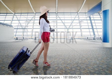 Female traveler walking in the airport terminal while carrying a luggage and wearing hat with digital camera on her neck