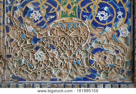 Piece of the old mosaic on the wall of an ancient building of Registan square, Samarkand, Uzbekistan