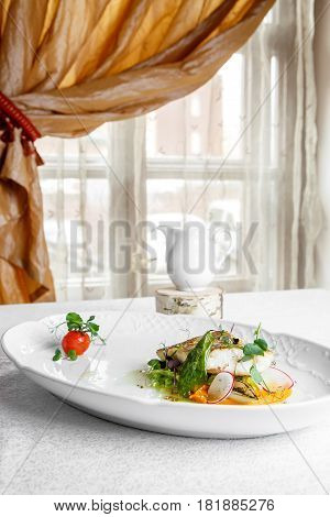 Fish dish - fillet of zander in plate on the table near window served with tomato radish and milk sauce