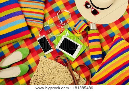 Summer picnic. Mobile phone electronic book hat and bag on the picnic mat. Selective focus.