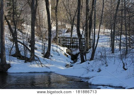 Little wooden bridge spanning a deep crevice full of rocks, water, and snow, in an area filled with snow and trees during the winter season