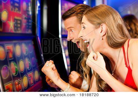 Couple in Casino on a slot machine