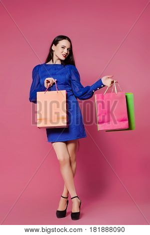 Shopping woman holding shopping bags l on a pink background