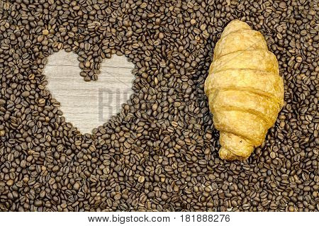Coffe bean background with heart and croissant on table
