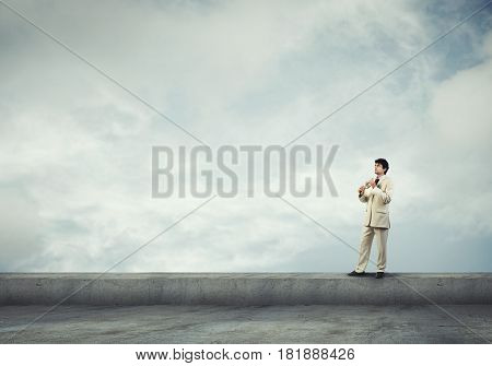 Young businessman on building top playing trumpet