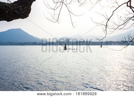 Landscape with the lake, boat, pagoda and mountains. Beautiful Hangzhou West lake scenery, Leifeng pagoda in afterglow.