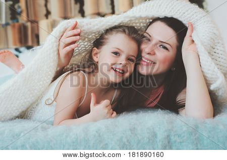happy family playing at home. Mother and toddler daughter relaxing and having fun in bed in cozy weekend morning