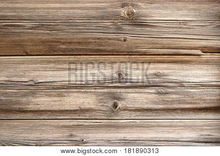 Old wood fence made of aged planks. Cracked planks background in vintage style.