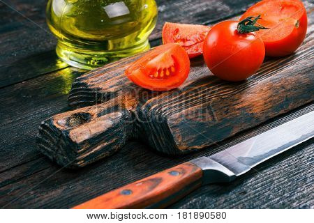 Fresh tomatoes on rustic wooden cutting board and olive oil in cruet on old dark wood table. Close-up angle view
