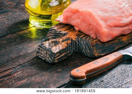 Raw pork meat loin on rustic wooden cutting board with olive oil in cruet on old dark wood table. Close-up angle view