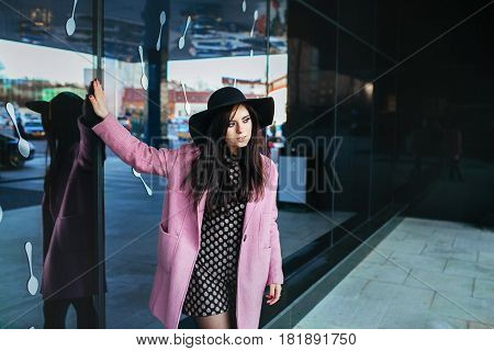 Outdoor portrait of a young beautiful fashionable woman walking on the street. Model wearing stylish pink coat, black hat . Model looking aside. Female fashion concept