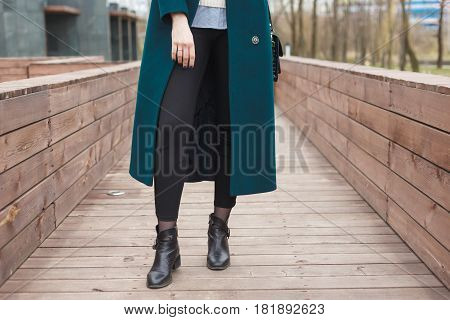 Black ankle boots, black leather bag, warm emerald coat and black trousers. Stylish and fashionable girl on a walk.