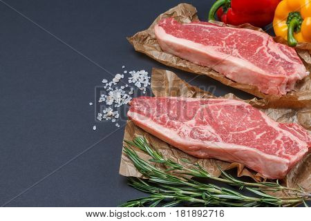 Two raw slice of Striploin steak with salt, rosemary and sweet pepper for good supper