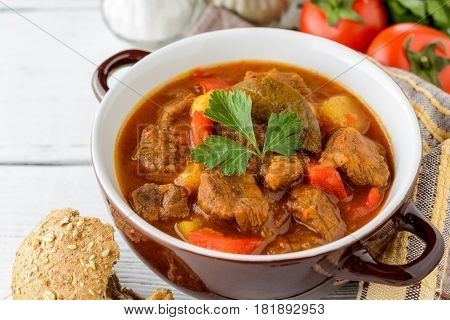 Goulash in ceramic bowl on white wooden background. Traditional hungarian soup. Rustic style. Selective focus.