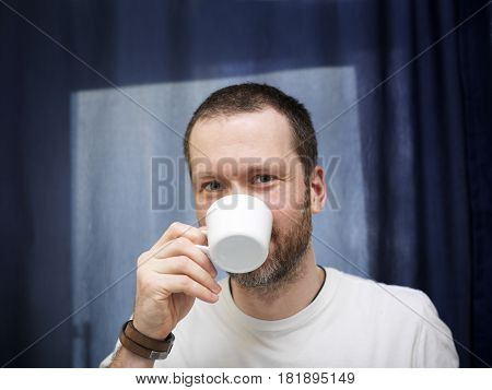 Mid aged man looking happy tasting coffee. Window and curtain in the background