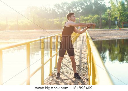 Jogger warming up exercising, stretching arms and shoulder. Fitness, sport on fresh air