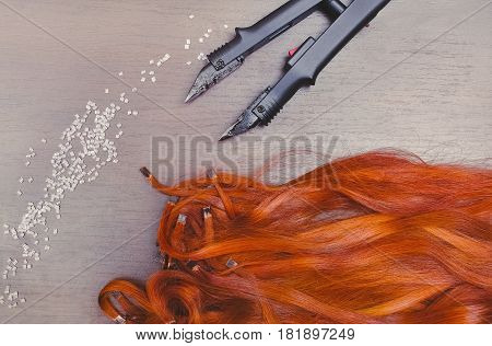 Pre Bonded keratin capsules of Red hair extensions close to keratin capsules and Hair Extension Iron on the a wooden table