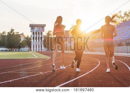 Rear view of women athletes running together in stadium