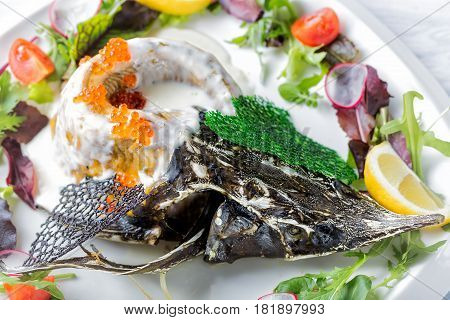 Sturgeon baked in a creamy sauce with lemon caviar garnished with greens on a white plate close up.