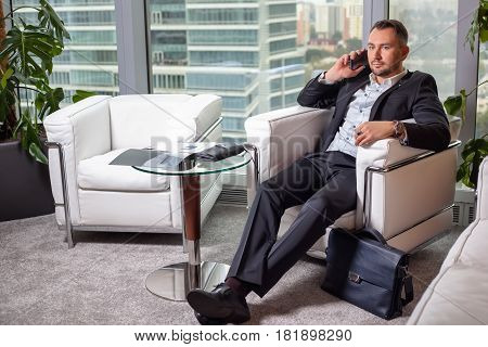 Businessman in suit talking on mobile phone sitting in an easy chair in the office