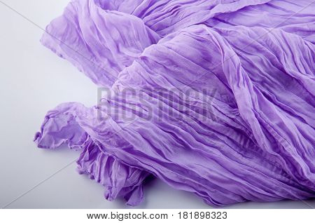 Part of purple soft wrinkled semitransparent fabric on white background