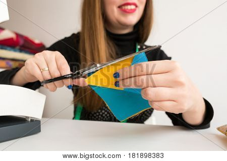 needlework and quilting in the workshop of a young woman, a tailor on white background - hands of a woman tailor at work with scissors and the pieces stitched in blue and yellow fabrics of patchwork