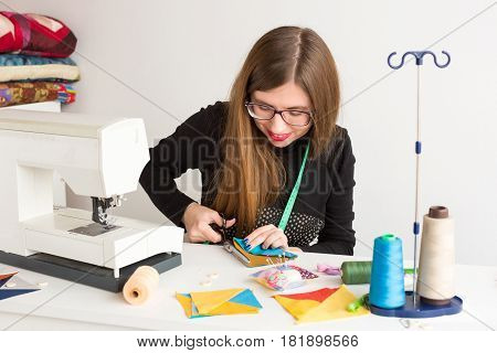 needlework and hand quilting in the workshop of a young tailor on white background - woman cuts with scissors stitched fabric at the desk with a sewing machine, spools of thread and pin cushion