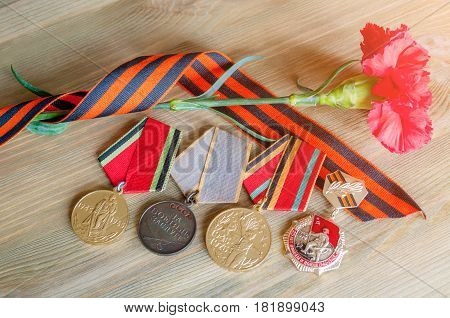VELIKY NOVGOROD RUSSIA - CIRCA APRIL 2017. 9 May background with medals of Great patriotic war red carnations and George ribbon. 9 May Victory Day concept