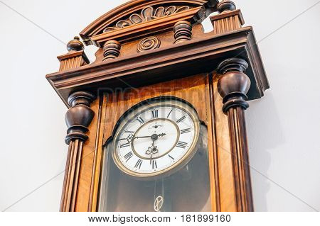 Old vintage woden clock on white wall