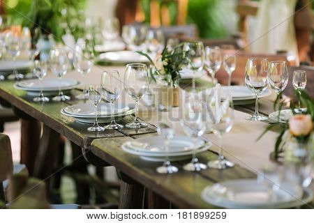 Glasses on the festive table setting. Wedding table decor concept. Table setting in classic style, setout. fine art.