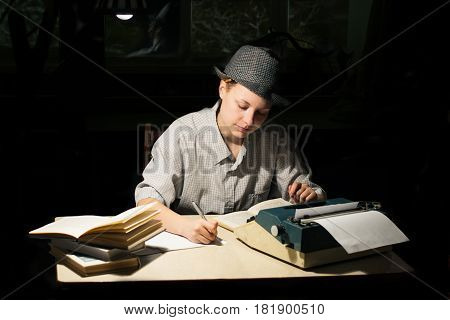 Portrait of a girl in a hat sitting at a table with a typewriter and book making notes at night