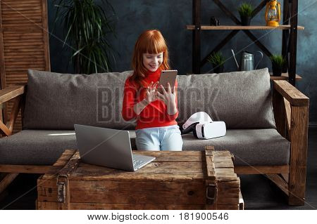 Beautiful little red-haired girl sitting on sofa in room and flipping smartphone