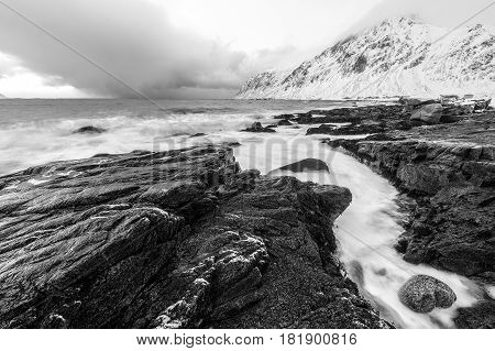 Magnificent snow-covered rocks on a sunny day. Beautiful Norway landscape. Lofoten islands. Black-white photo.