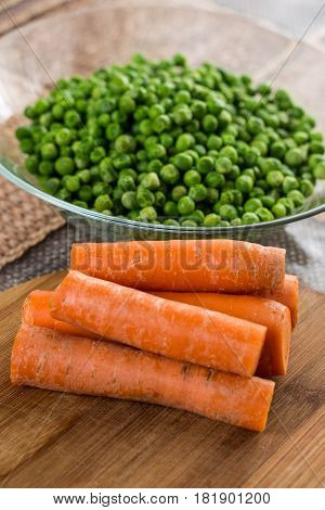 Cooked Green Peas With Cooked Carrot On The Wooden Board