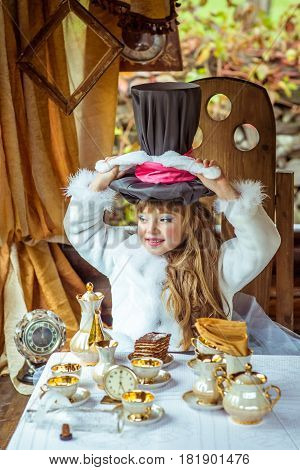 An little beautiful girl in the scenery of Alice in Wonderland holding cylinder hat with ears like a rabbit over head at the table in the garden.