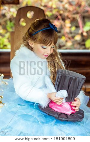 An little beautiful girl in the scenery of Alice in Wonderland holding cylinder hat with ears like a rabbit in the hands at the table in the garden.