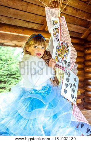 An little beautiful girl in a long blue dress in the scenery of Alice in Wonderland playing and dancing with large playing cards on the table in the garden.