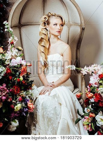 beauty emotional blond bride in luxury interior dreaming, crazy complicate hairstyle, spring flowers