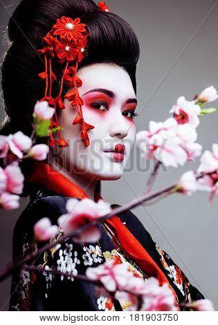 young pretty geisha in kimono with sakura and decoration close up