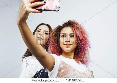 lifestyle people concept: two pretty stylish modern hipster teen girl having fun together, diverse nation mixed races, happy smiling making selfie close up