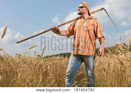 Modern farmer with scythe at ripe wheat field