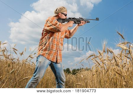 Hunter at cap and sunglasses aiming gun at field