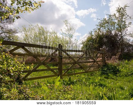 A Glorious And Stunning Wooden Gate And Fence In The Countryside Closing Off A Farm Field With Lush