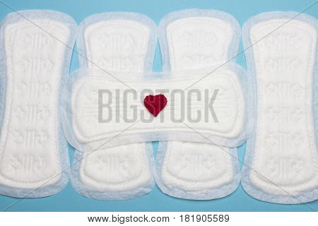 Heap of menstruation sanitary soft cotton pads and cotton tampons for woman hygiene protection. Woman critical days gynecological menstruation cycle. Crochet red heart. Medical hygiene conception
