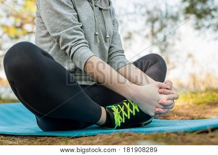 Girl in a sport suit outdoors meditating on a blue sports mat