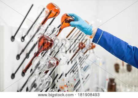 Many glass beakers on the hangers on the blurry background in the lab. Some of them are transparent, other are brown. Hand in blue gloves holds one of them. Closeup. Horizontal.