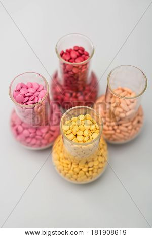 Four glass flasks with many colorful placebo pills on the light surface. Pills are yellow, orange, red, pink and have different size and form. Closeup. Vertical.