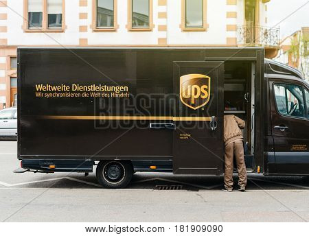 KEHL GERMANY - APR 6 2017: Worldwide delivery parcel - UPS United Parcel Service van delivery brown UPS van parked on a street with driver worker searching for the parcel in the van interior