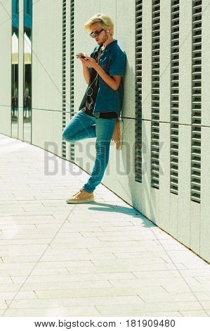 Men fashion technology urban style clothing concept. Hipster guy standing on city street wearing jeans outfit and sunglasses listening to music and looking at phone