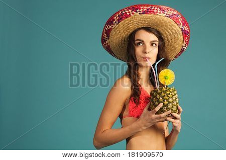 young beautiful woman in bikini and sombrero drinking tropic cocktail looking up left isolated on blue background